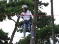 Adolescente sur un parcours aventure dans les arbres